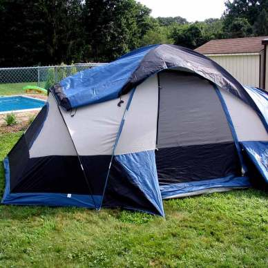 Picutre shows a gray, blue and black tent set up in the backyard of someone's house.