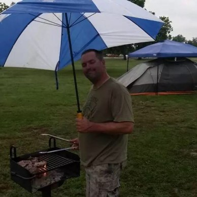 Picture shows a man standing at a barbeque grill in the rain with a large umbrella. A tent with a pop up sun shade is in the background.