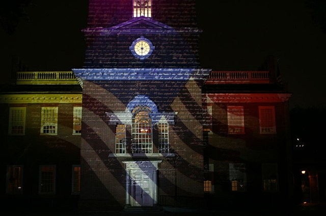 An American flag and the Declaration of Independence lights up Independence Hall in Philadelphia.