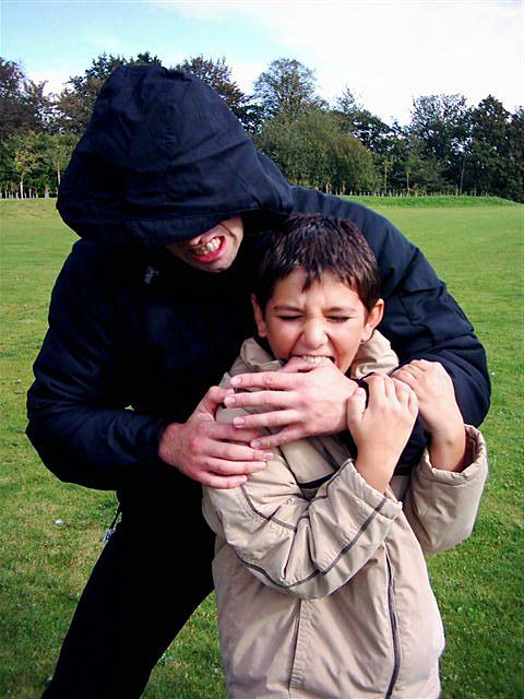 Attacker grabbing young boy