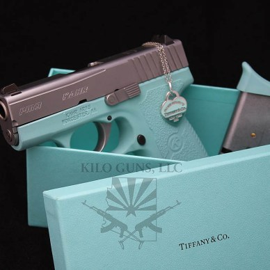 """Picture shows a Kahr Arms handgun finished in """"Tiffany blue"""" laying in a box from Tiffany and Co."""