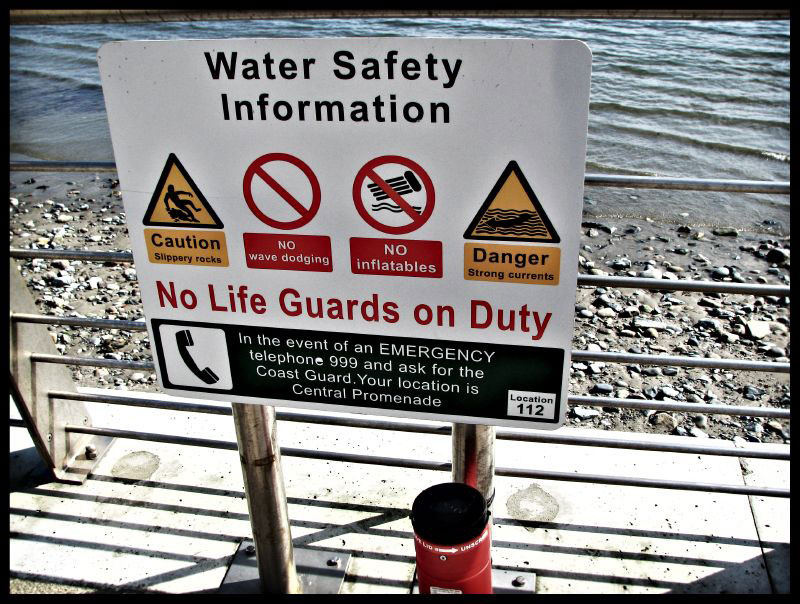 Picture shows a safety sign on the dock next to a rocky beach on the lake.
