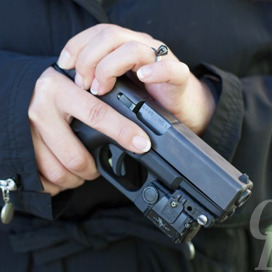 Picture shows a woman holding a Glock safely, finger off the trigger close into her body at the bottom of her chest.