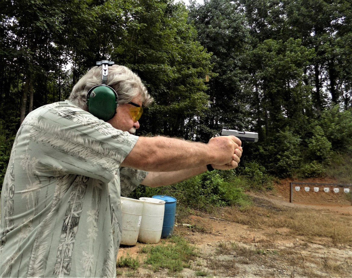 Bob Campbell shooting a pistol with a two-handed grip