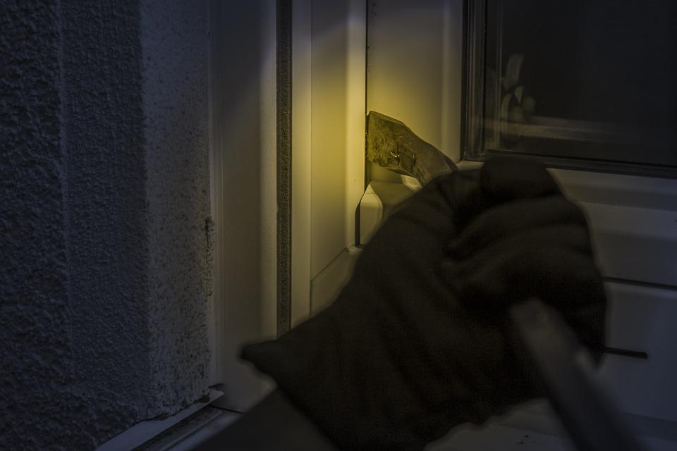 burglar using a crowbar to break into a house
