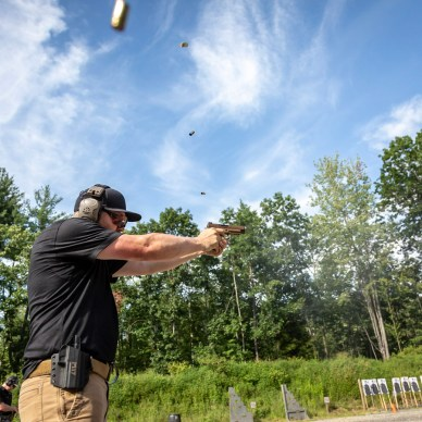 Shooting a pistol with four cartridge cases in the air