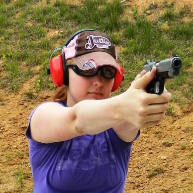 Woman shooting a semi automatic handgun wearing a pink and brown ballcap