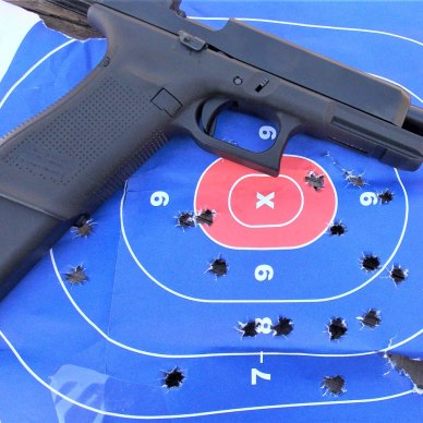 Glock pistol with 33-round magazine inserted on a blue and red target