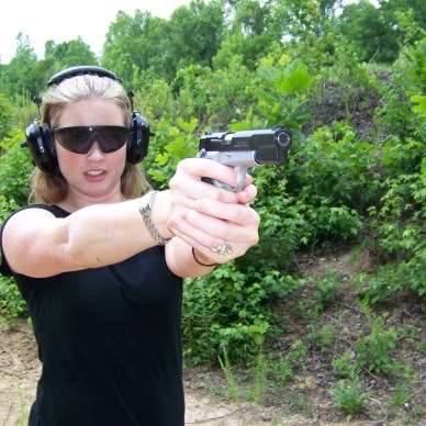 Woman shooting a Browning Hi Power with a two-handed grip