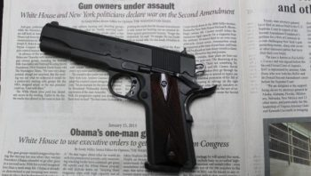 1911 pistol on top of newspaper