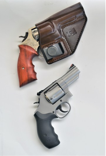 Two revolvers in leather holsters