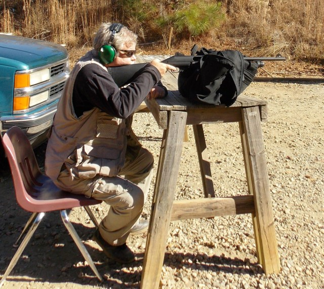 Author shooting a shotgun from a bench rest position