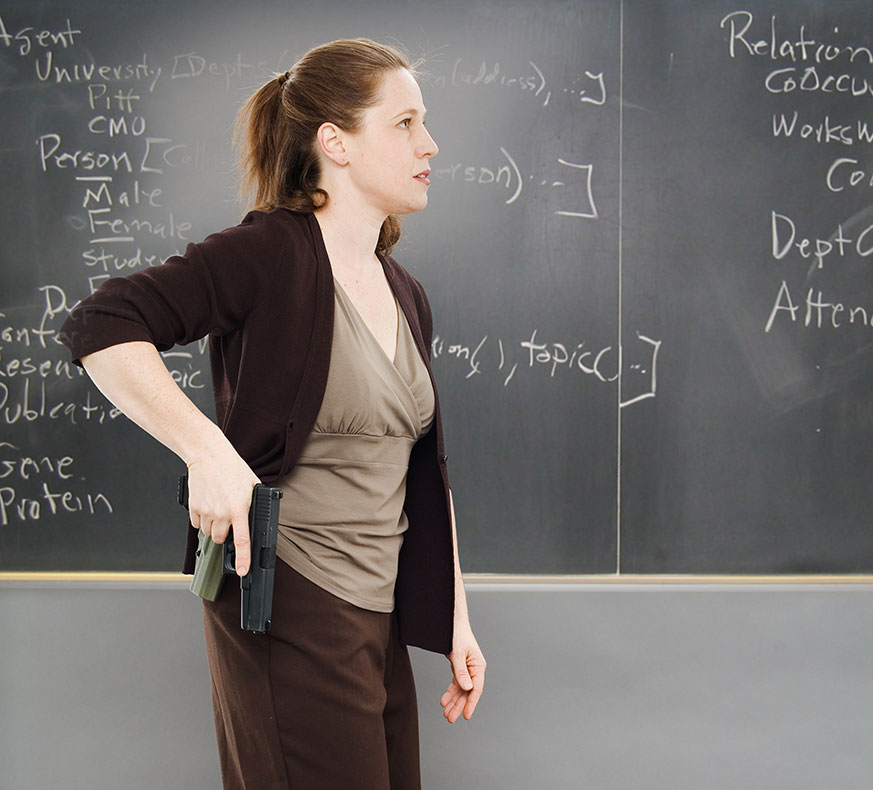 Teacher in front of a blackboard drawing a pistol from a holster.