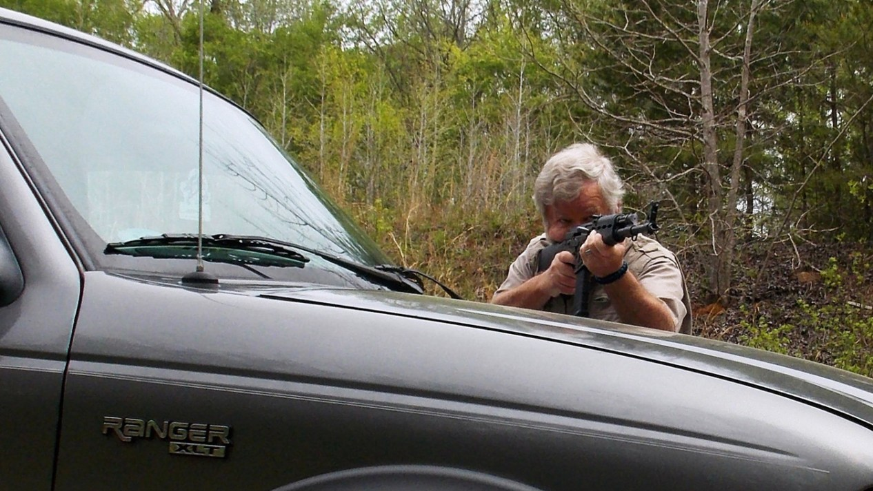 Bob Campbell shooting an AK-47 rifle over the hood of a pickup truck
