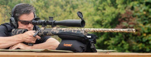 Man shooting rifle rested on bag