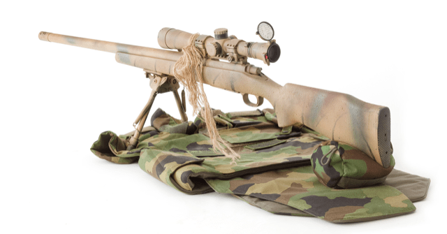 Bolt action rifle on camo mat