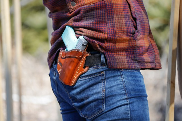 concealed carry handgun in leather holster on hip