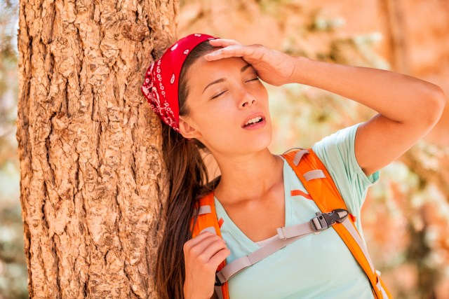 Dehydrated tired hiking woman thirsty feeling exhausted of heat stroke. Girl with headache from hot temperature on outdoor activity hiker lifestyle.