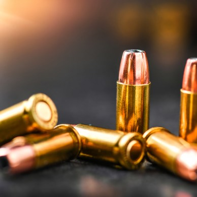 Bullets ammunition on stone table wide banner or panorama. Bullet background copy space. Rounds and ammo into 9mm hand gun.