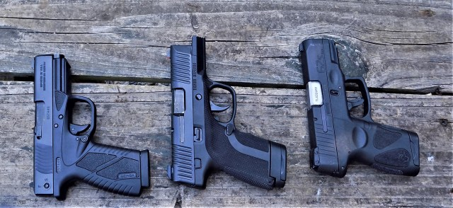three semi-auto handguns on wood table