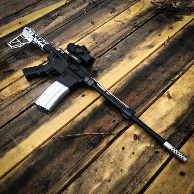 silver and white AR-15 rifle on wood floor