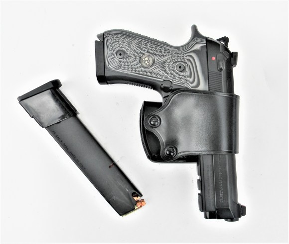 Beretta pistol in holster with spare mag