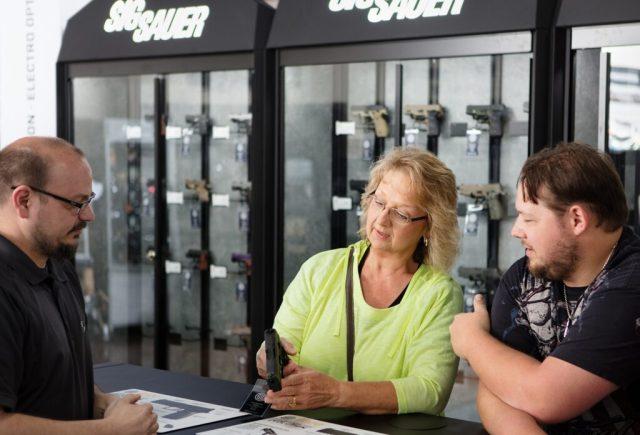 woman looking at new handgun at counter