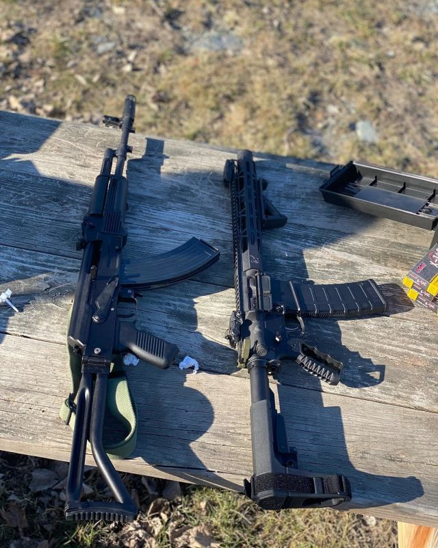 AK and AR rifles on wooden range bench