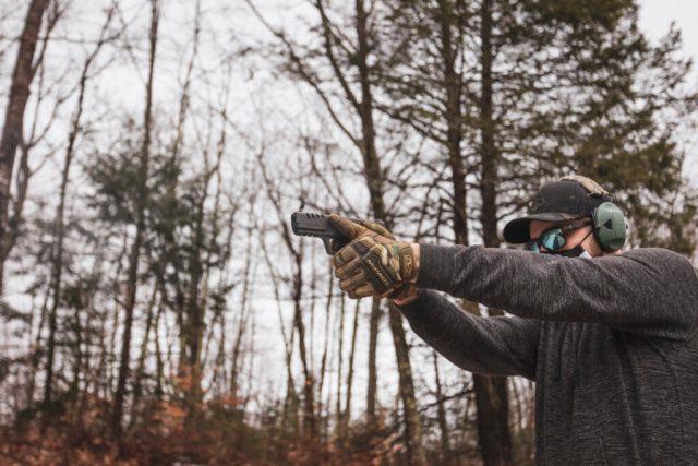 Man Shooting Pistol in Woods