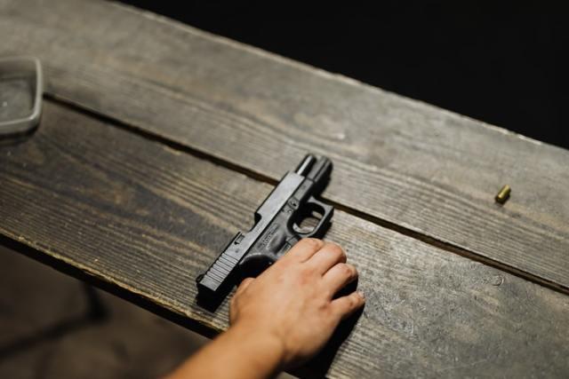 handgun with hand on bench first gun