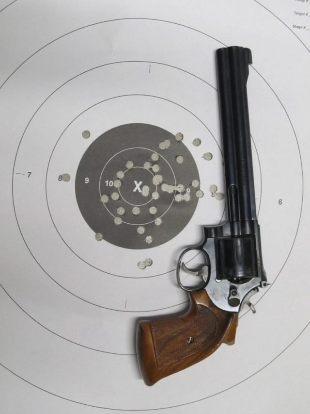 Vintage S&W revolver on target with holes