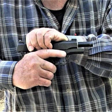 man racking slide on pistol