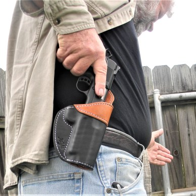 man drawing pistol from holster