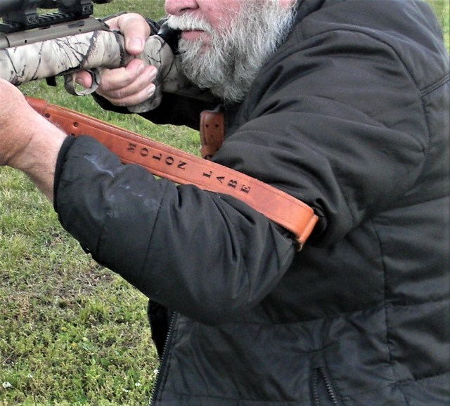 man firing rifle with sling support