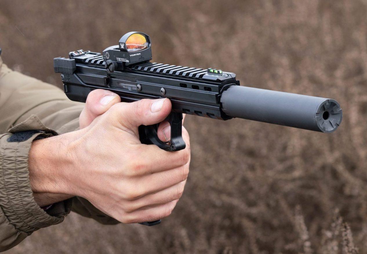 Man shooting kel-tec CP33 pistol with red dot