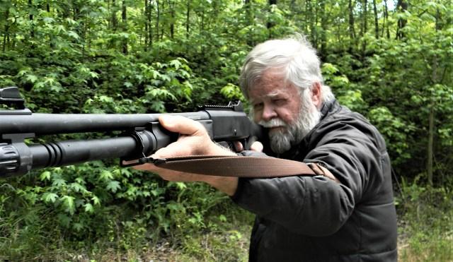 man firing shotgun with sling support