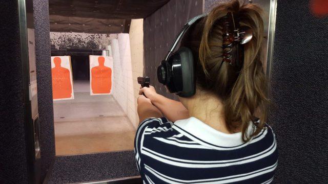 woman shooting handgun at range recoil