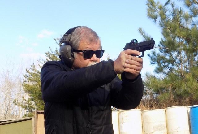 man shooting SIG P229 RX pistol