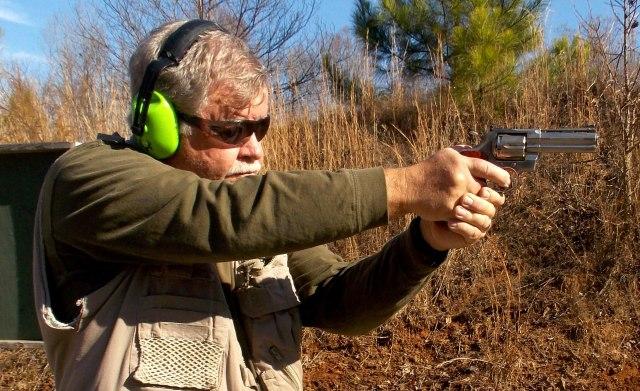 man shooting in field
