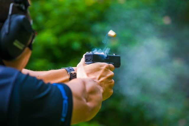 Shooting from a pistol. Reloading the gun. The man is aiming at the target. Shooting range recoil