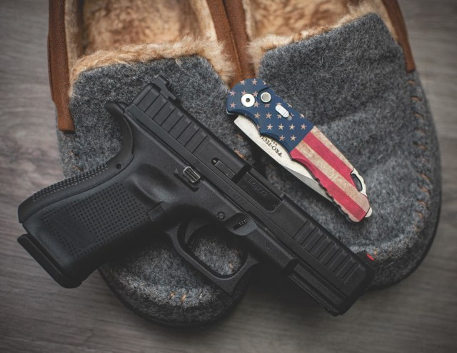 Glock 44 pistol on slippers with pocket knife