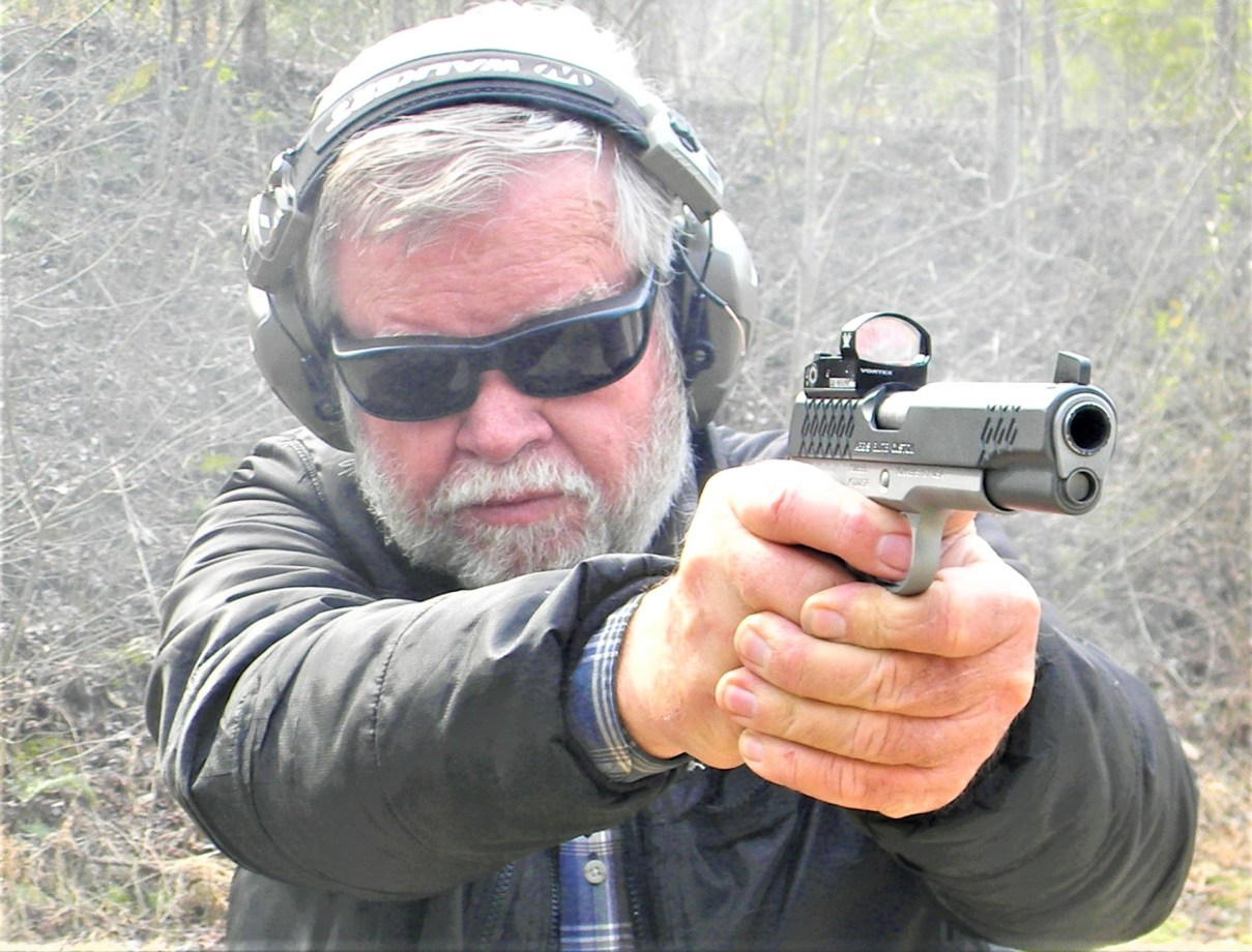 man shooting pistol with red dot