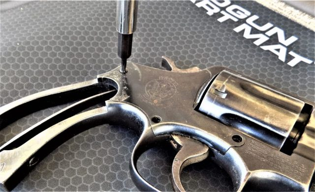 fieldstripped revolver and screwdriver