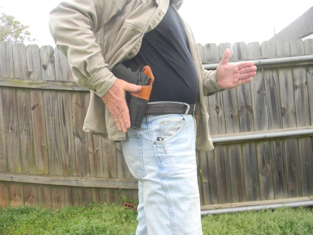 man drawing pistol from concealment