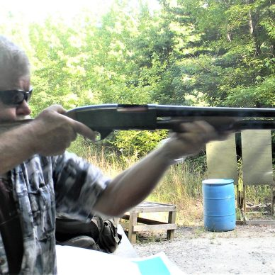 man shooting pump-action shotgun