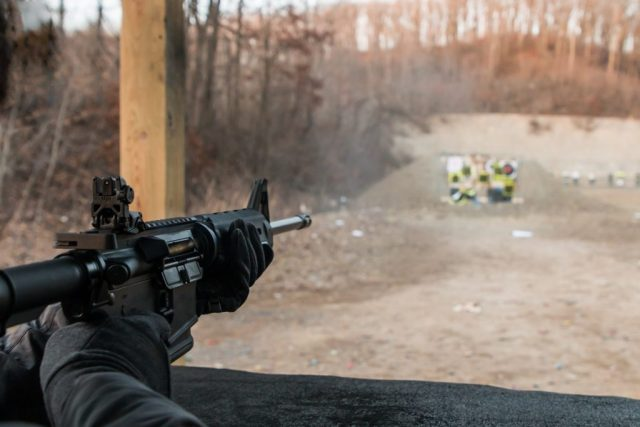 Person shooting a semi-automatic AR-15 assault weapon rifle at an outdoor gun range