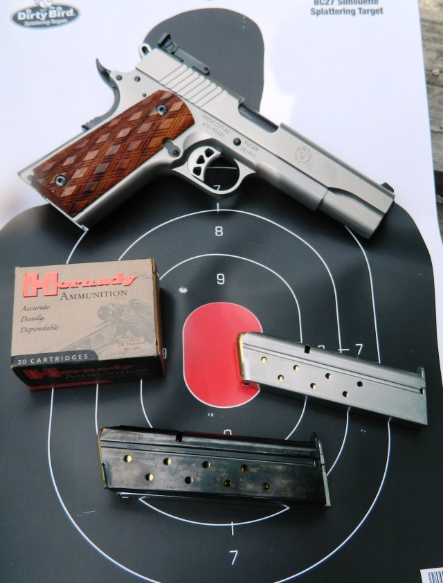 1911 pistol on target with magazines and ammo box