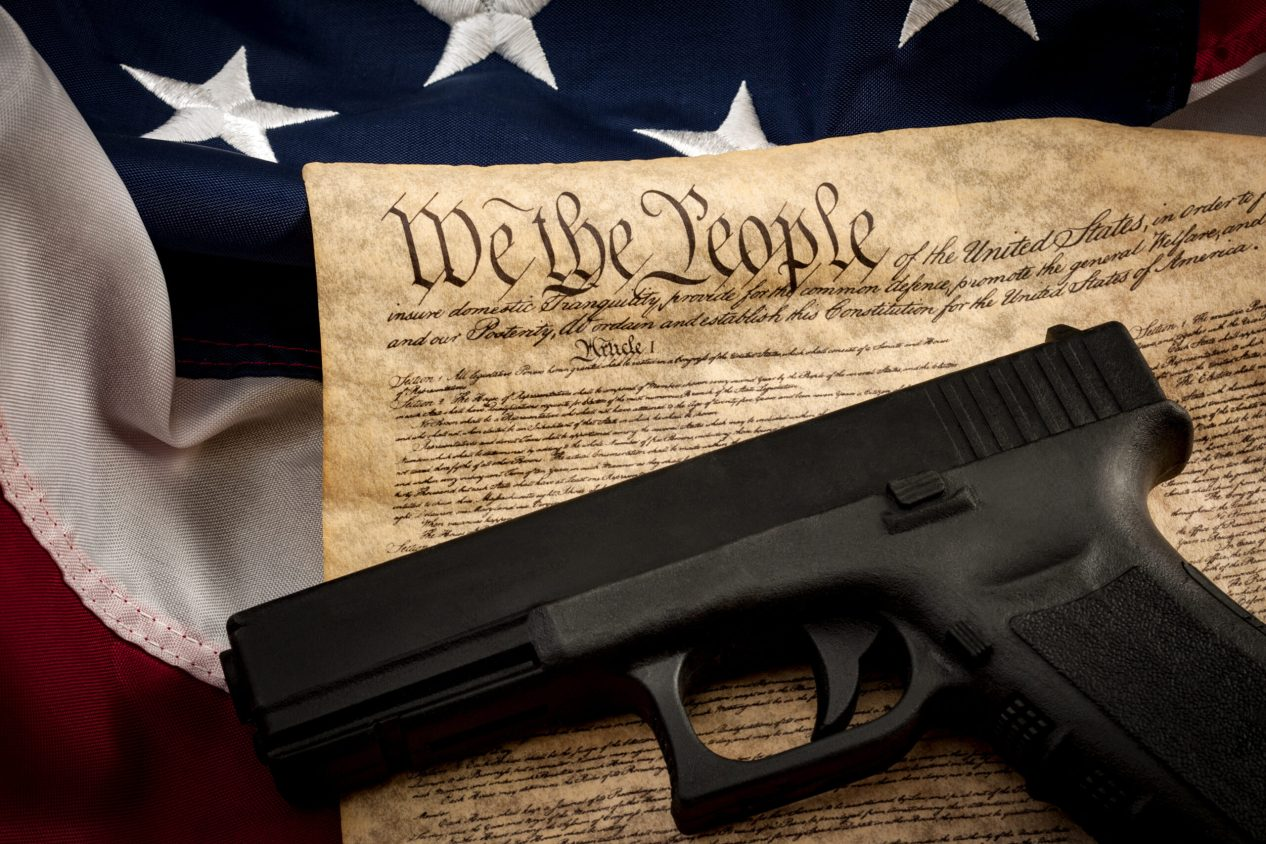 """The second amendment and gun control in america concept with a handgun and the american constitution on the USA flag with close up on the """"we the people"""" part of the united states constitution"""
