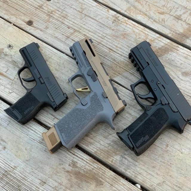 Three SIG pistols on wood