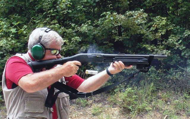 bob campbell shooting a Remington shotgun with a spent hull in the air and smoke emitting from the ejection port